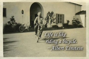 Vintage photo of Albert Einstein riding a bicycle with quotation overlayed