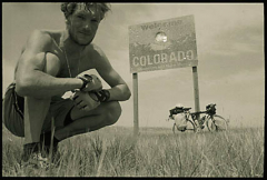 """Forrest MacCormack kneeling beneath the """"Welcome to Colorado"""" during his bike tour in 1997."""