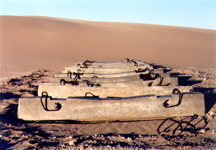 Railroad ties disappear into the sand dunes.