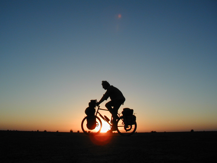 Alastair Humphreys with the setting sun perfectly behind his silhouette.