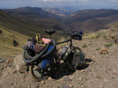 The bicycle that went around the world perched on the edge of a scenic cliff in the Drakensburg Mountains, Lesotho, Southern Africa.