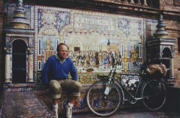 Heinz Stucke sitting in front of a colorful mosaic.