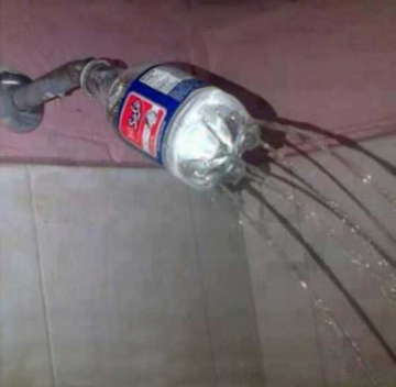 A water bottle with holes poked into it is attached to a shower head to make a sprinkler.
