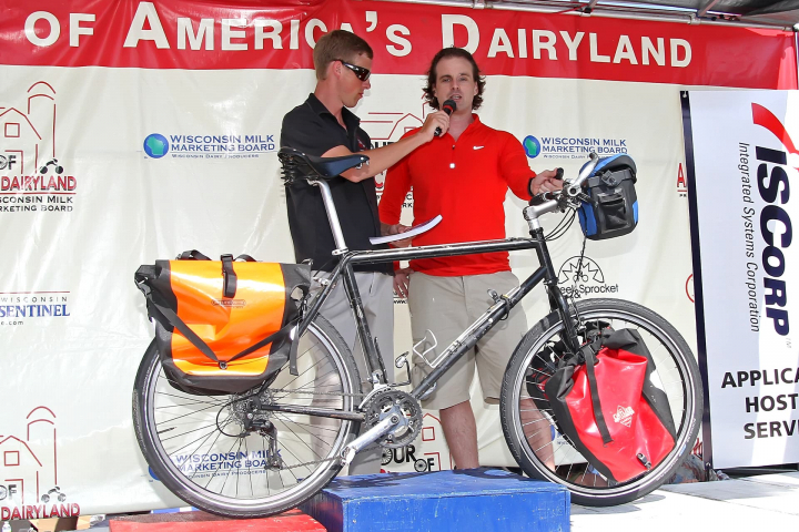 Scott Stoll being interviewed while his bicycle is on the red, white and blue podium, occupying first, second and third place.