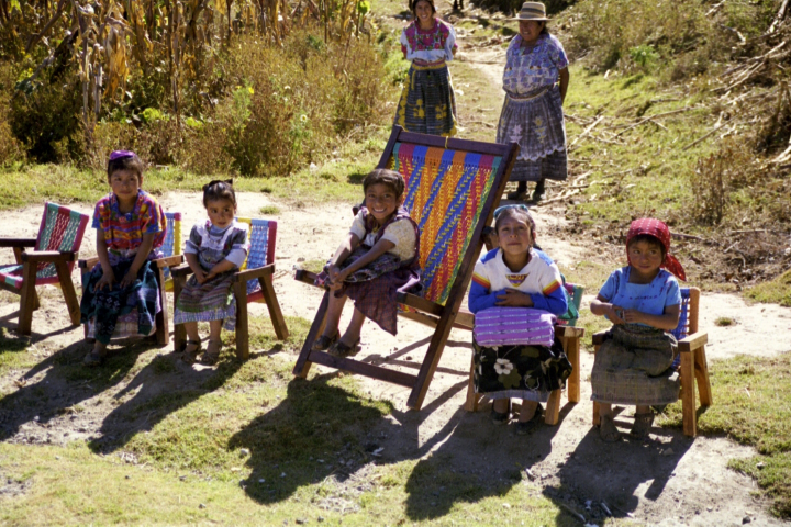 Picture-perfect. Adorable girls in Guatemala dressed in colorful clothes sitting on colorful, woven chairs.