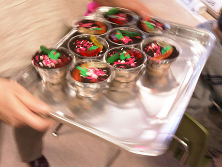 Colorful Gummi worm cupcakes being served on a silver platter.