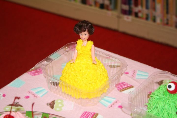 Cinderella cupcake. The top half is a doll with a dress of yellow frosting.
