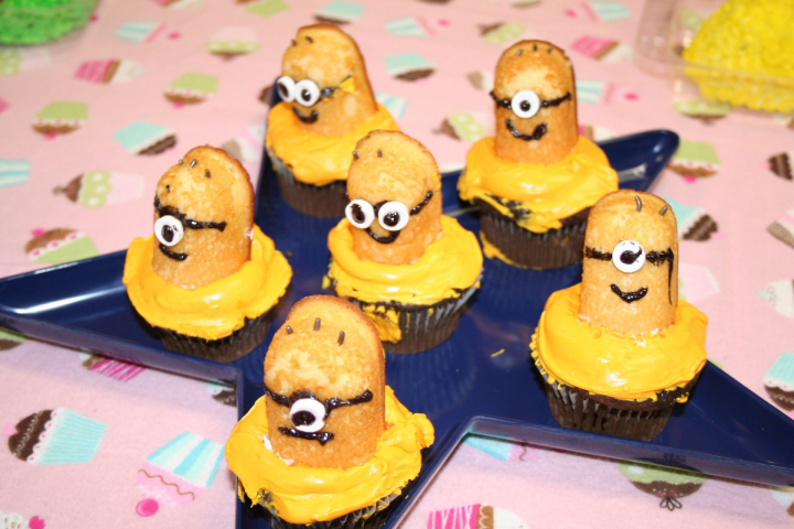 Yellow Minion cupcakes made out of Twinkies on top of a cupcake base with lots of yellow frosting.