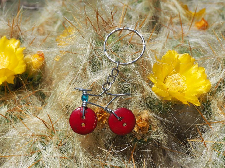 Wire, bead and red buttons made into a bicycle-shaped keychain. Artistically photographed on top of a cactus.