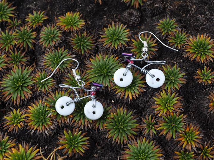 Martina Gee's Velobotóns Earrings. Wire, beads and white buttons made into decorative bicycle-shaped earrings.