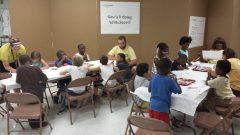 """The """"How's it going"""" Dream Workshop station with facilitators and children."""