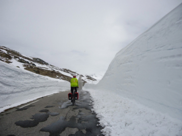 marc jason bicycle tourer riding down a road with steep snow banks