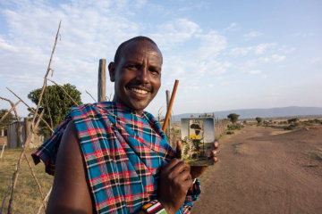 Maasai man holding photo of Rachel Hugens and Patrick on the Kenya Equator.