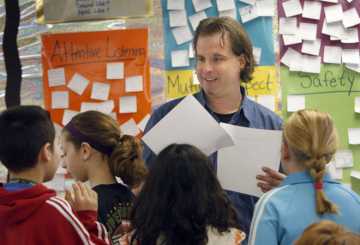 """Scott Stoll hands out pages with excerpts from his book, """"Ruby the Red Worm's Dirty Job,"""" to students at the Waukesha STEM Academy's Randall Campus this week. Students are drawing illustrations for the book. Photo by Wentz-Graff, Milwaukee Journal"""