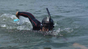 Ben Lecomte swimming in the ocean with flippers and fancy snorkel like a dorsal fin but going between the eyes.