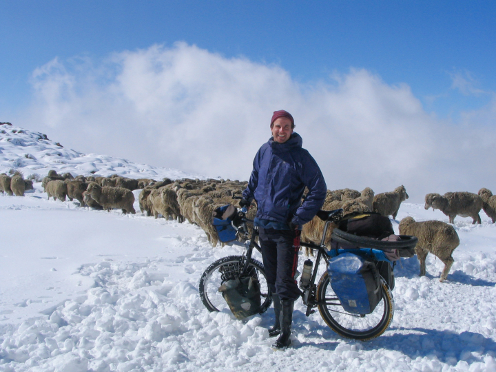 Scott Stoll and touring bicycle pictured in deep snow surrounded by a flock of sheep.