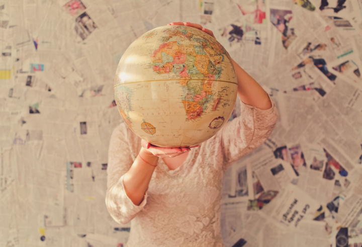 The world is your oyster. By Slavman. A woman holding a globe and dreaming of traveling the world.