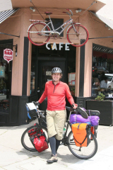 Scott poses in front of a bicycle cafe with his bicycle matching the bicycle sign hanging over the door.