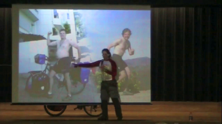 Scott on stage pointing to a before-and-after picture of himself from his trip around the world on a bicycle.