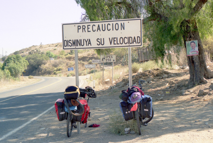 "Two bicycles leaning against a road sign in Baja Mexico that says, ""Precaucion Disminuya Su Velocidad."" In English, ""Caution Reduce Your Speed."""