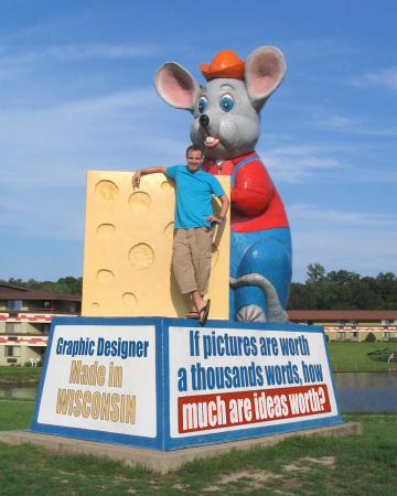 "Scott standing next to a giant mouse and hunk of cheese. He used his graphic design skills to change the sign to read: Graphic designer. Made in Wisconsin."" And on the other side it says, ""If pictures are worth a 1000 words, how much are ideas worth?"""