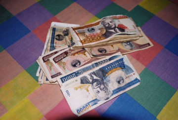 Vietnamese money, called Dong, piled on a colorful bed spread.