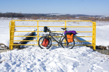 Scott's bike with colorful panniers leaning against a yellow fence in a snowy field.