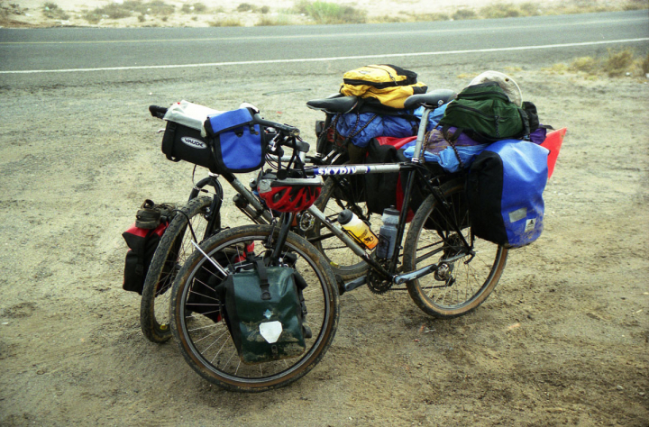 World touring bicycles loaded with supplies lean against each other in the early morning fog. Kickstands are one of the items we left behind.