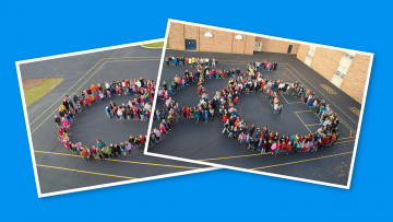 Over 500 children and teachers standing on the playground in the shape of giant bicycle.