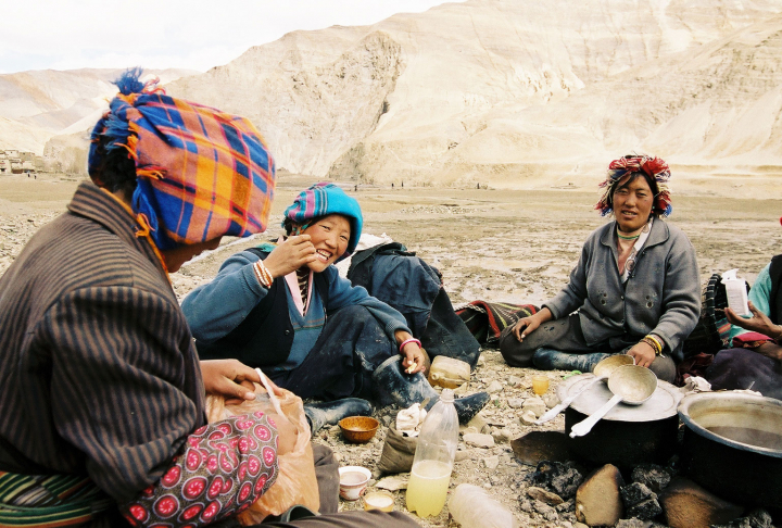 A group of colorful women in Tibet share their lunch. We sit in the rocky soil surrounded by barren hills.