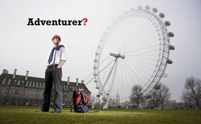 Tim Moss wearing climbing gear and a suit tie while standing in front of the London Eye.