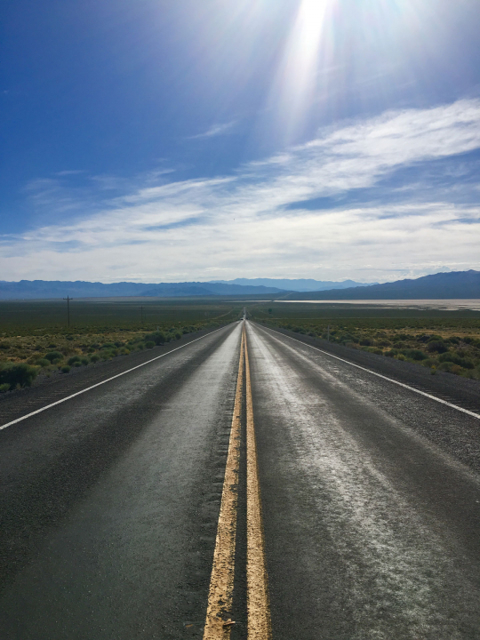 A black top road disappearing into the horizon and glaring sun.