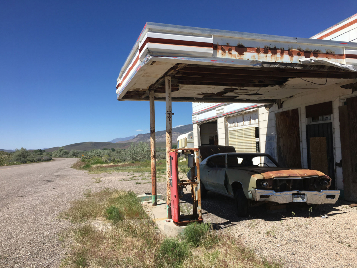 """An abandoned gas station and car. The rusted and sun-faded building are beautiful pieces of """"road art""""."""