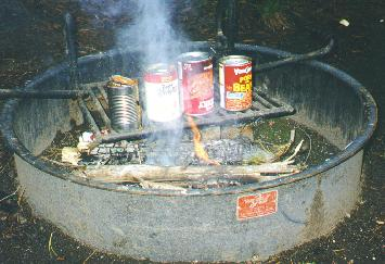 Cans of food being cooked on the campfire