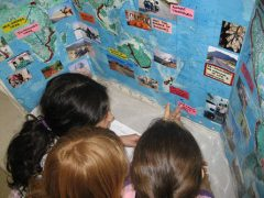 Elementary students looking the map of Scott's adventures