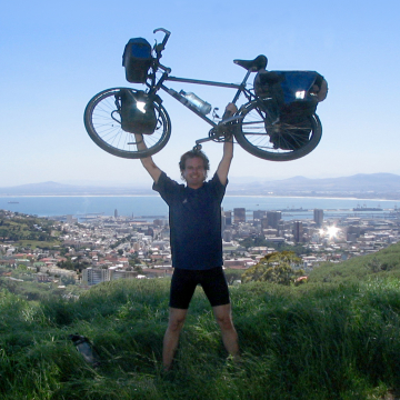 Scott Stoll profile picture avatar. Holding his fully-loaded touring bicycle over his head in a triumphant pose on top of Table Mountain, Cape Town, South Africa.