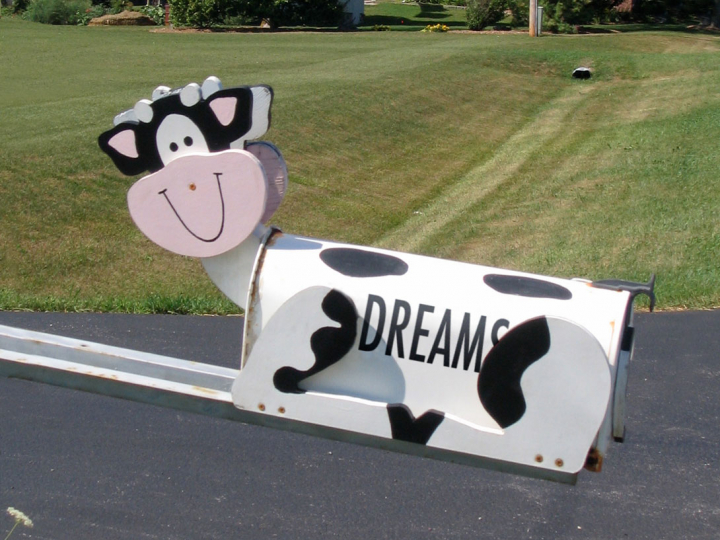 """A mailbox in the shape of a cow with the word """"dreams"""" written on the side."""