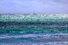 A colorful yet stormy sea Bahamas with a tiny sailboat on the horizon.