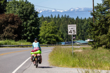 Rachel riding her bicycle down the road with pine trees and distant snow-capped mountains.