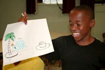 A student holds up a drawing with his solution of how to bridge the gap.