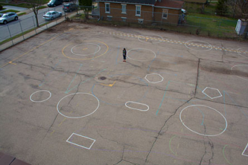 A teacher alone on the playground gets ready to line up the students. The words are invisible from the roof.