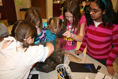 Students examine red worms and compost bin