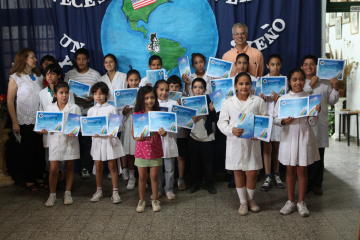 "Students from Argentina holding their certificates of achievements and their copy of ""Cayendo Hacia Arriba,"" the book that we created together."